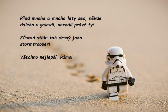 Bílá lego postava stormtroopera ze Star Wars jdoucí po poušti s nápisem.