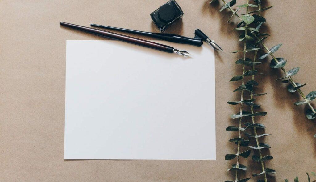 Bílý papír s perem a inkoustem.