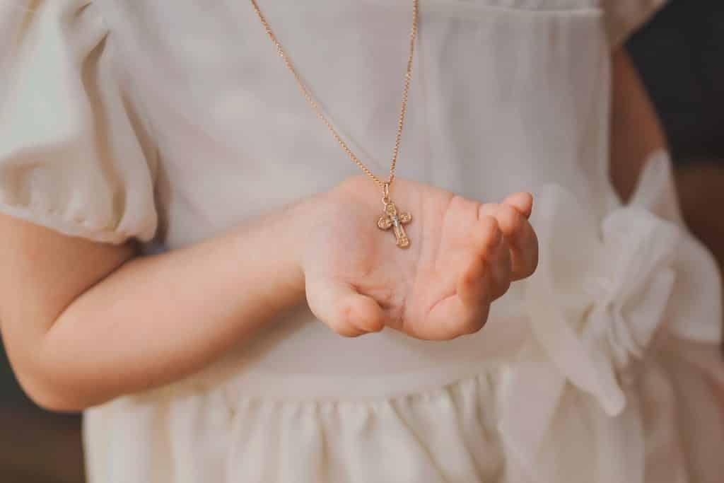 Zlatý křížek jako upomínka na svátost křtu.