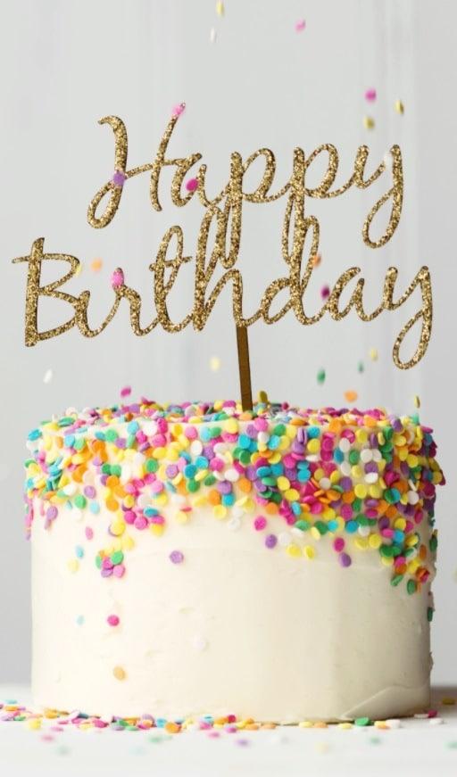 Narozeninový dort zdobený barevnými čokoládovými konfetami a se zlatým narozeninovým nápisem.