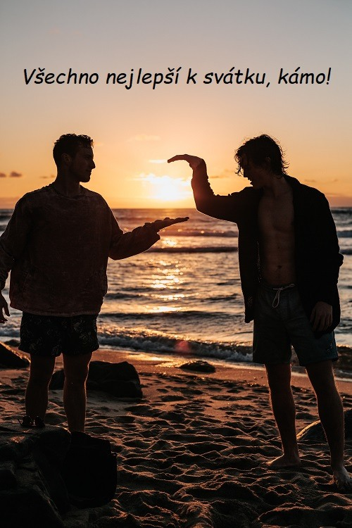 Dva muži na pláži, při západu slunce, podávající si ruce k pozdravu.