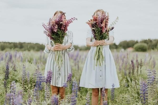 Dvě sestry držící čerstvě natrhané kytice na louce.
