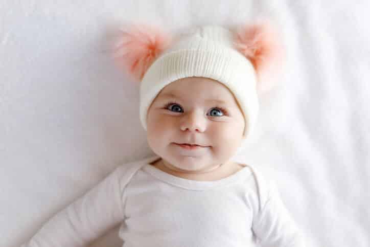 Miminko v bílém oblečení s čepicí.