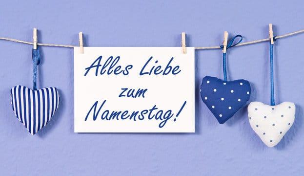 Bílá kartička s nápisem Alles Liebe zum Namenstag pověšená na špagátu se srdíčky z látky.