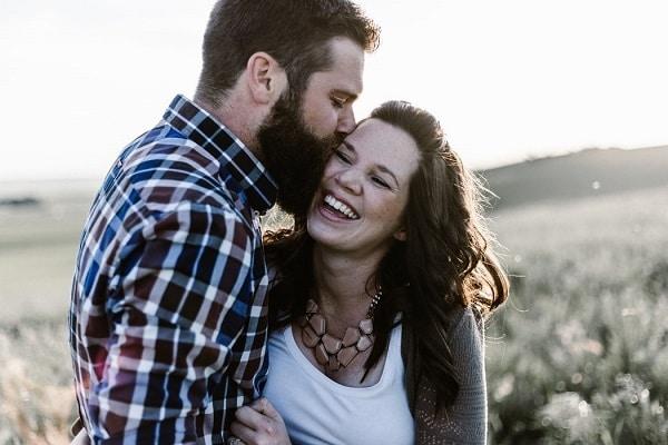 Muž, líbající smějící se ženu.