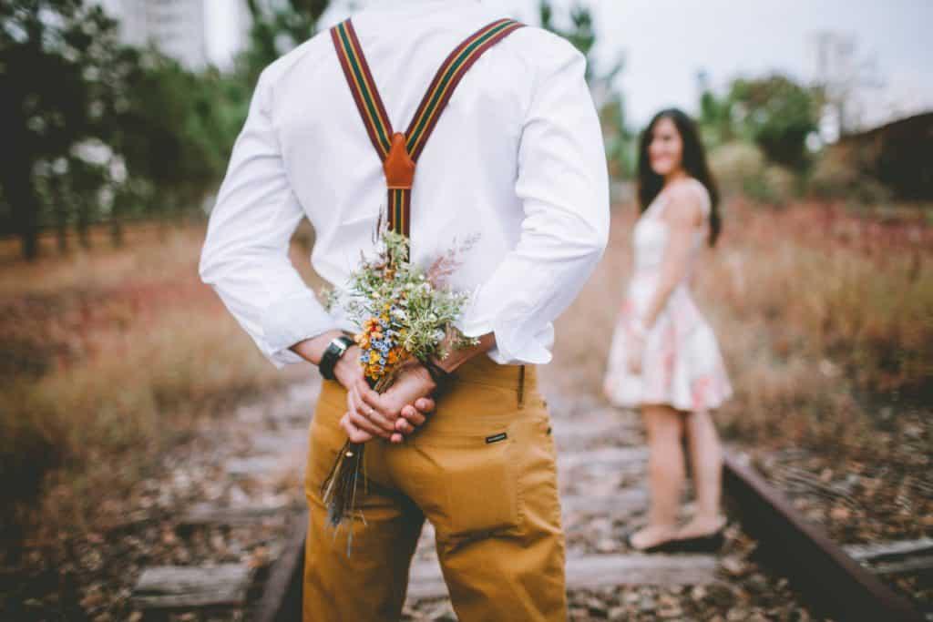 Muž nese krásnou kytici pro ženu pro lepší den.
