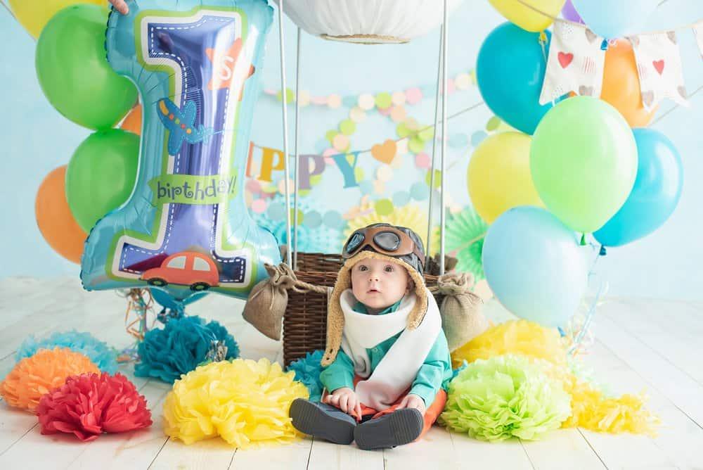 Chlapec sedící s balónky na narozeninové oslavě.