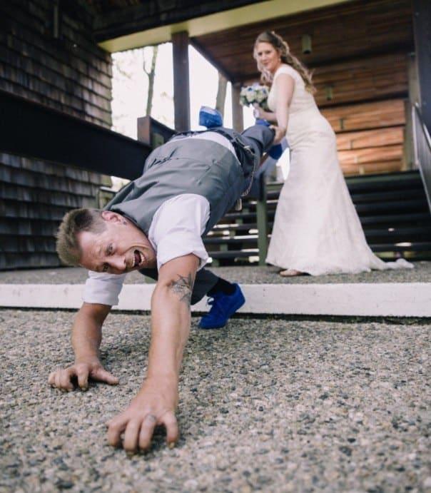 Nevěsta, tahající ženicha k sobě zpátky za nohu.
