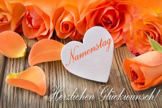 Oranžové přání k svátku v němčině s růžemi a se srdcem s nápisem Namenstag.