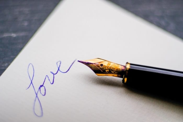 Papír s perem a nápisem love.