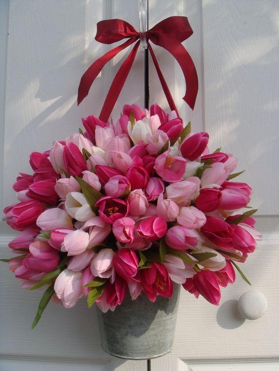Růžové tulipány v kyslíku zavěšené na dveřích.