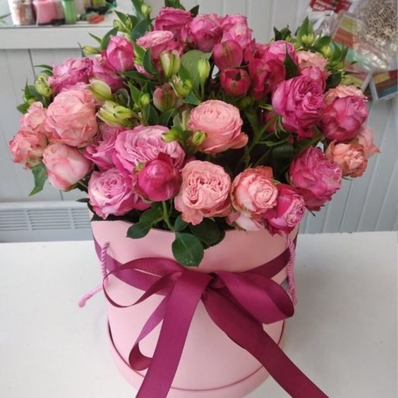 Kytice růží k svátku v růžové dárkové krabici.