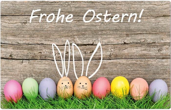 Řada barevných vajíček s obličeji zajíčků s ušima na dřevěném pozadí s nápisem Frohe Ostern!