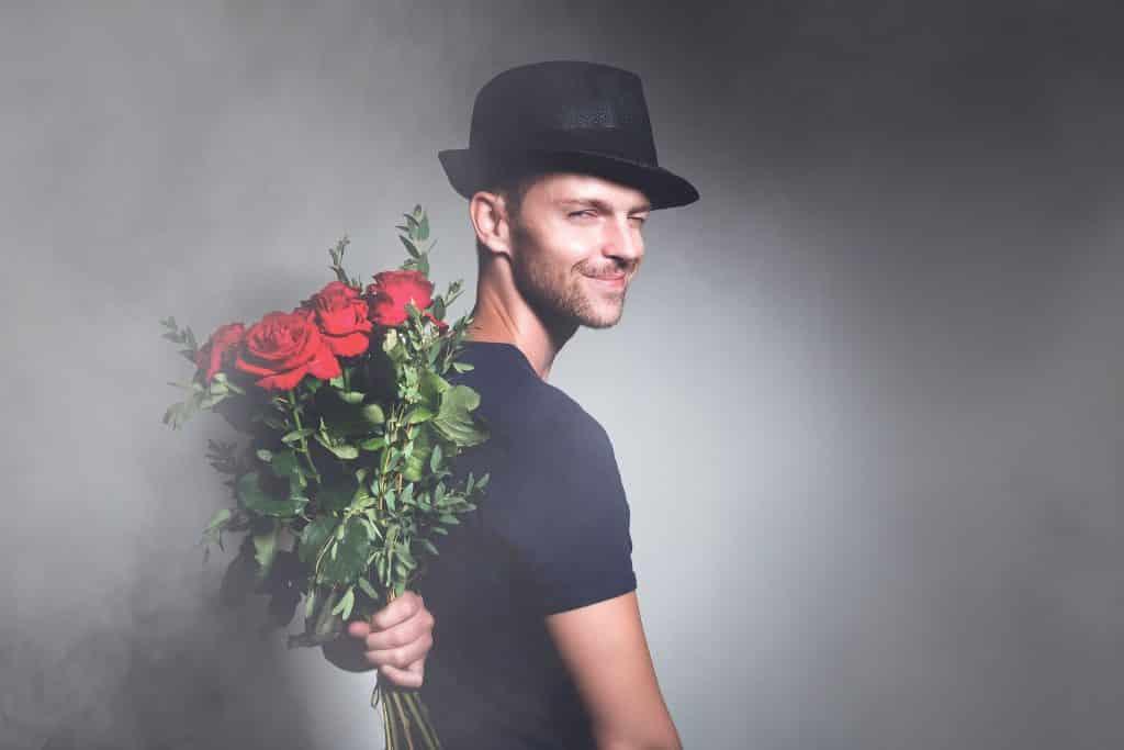 Muž s kyticí růží k narozeninám.