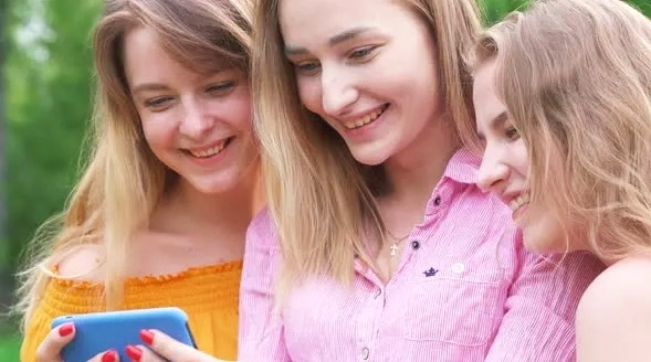 Tři smějící se dívky, dívající se na mobil.