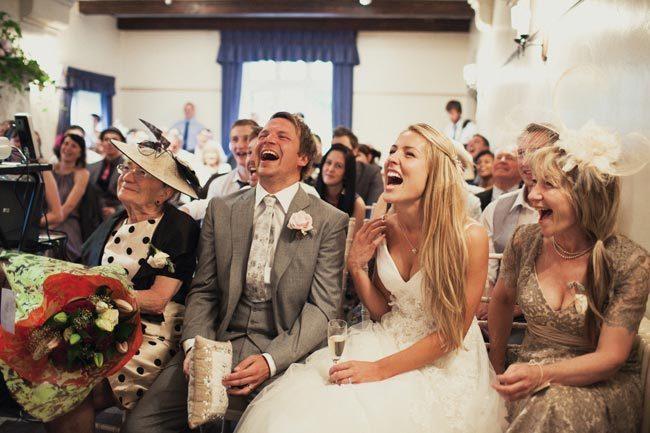 Smějící se novomanželé a hosté usazeni na hostině.