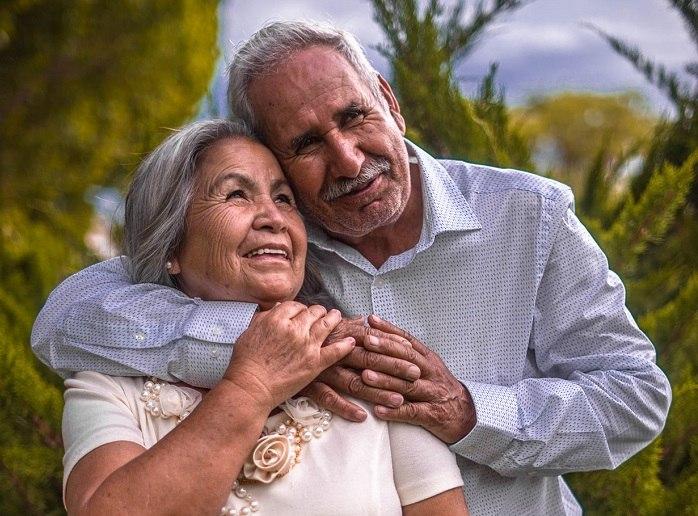 Starší usmívající a objímající se pár, hledící do nebe.