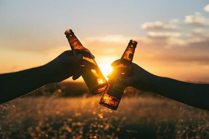 Ťukání s pivními lahvemi při západu slunce.