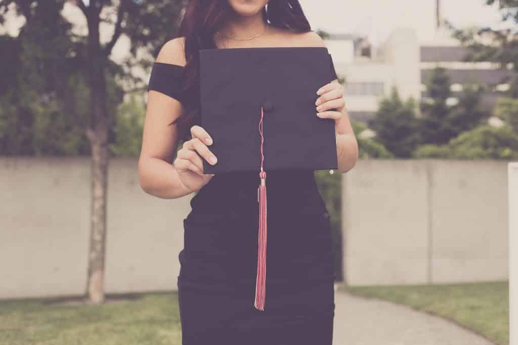 Tělo studentky držící slavnostní klobouk.