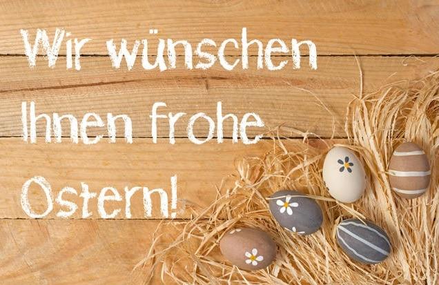 Velikonoční přání v němčině na dřevěném pozadí s malovanými vejci položenými na slámě.