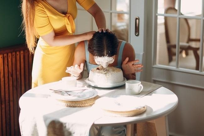 Žena ve žlutých šatech, namáčející obličej ženy v modrých šatech do narozeninového dortu.