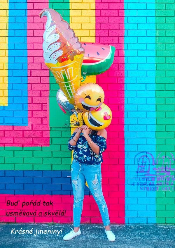 Žena s balónky ve tvaru zmrzliny, melounu a smajlíků.