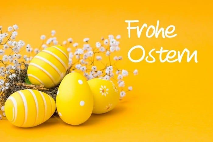 Krásná žlutá malovaná vejce na žlutém pozadí s květy a nápisem Frohe Ostern.